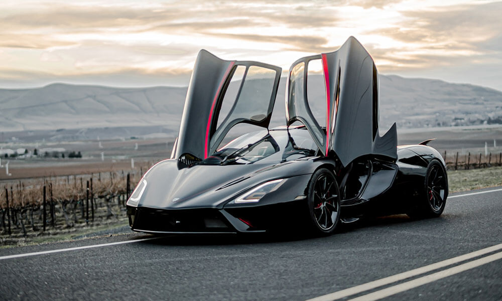 black SSC Tuatara hypercar with doors open on road at sunset
